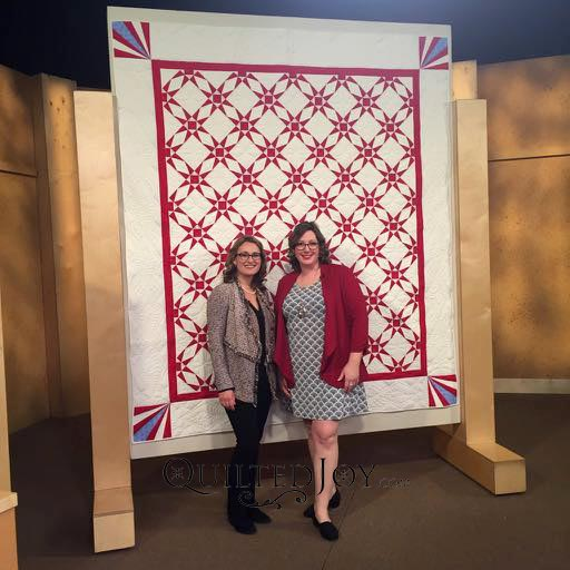 Angela Huffman and Sara Gallegos on the set of Fons & Porter's Love of Quilting standing in front of Angela's Patriot quilt