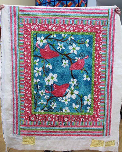 Kathy shows off her birds panel quilt after a longarm machine rental at Quilted Joy