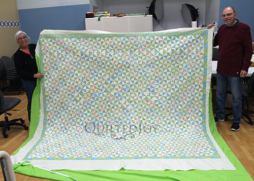 Dennis shows off his pastel colored Pinwheel Block Quilt after longarm quilting at Quilted Joy