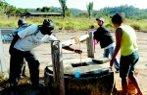 Imagem de pessoas retirando água de poço.