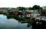 Imagem de casas construídas a beira de rio poluído com esgoto.