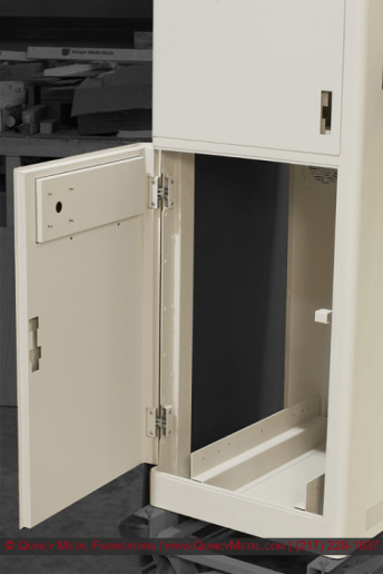 A precision electronics enclosure with comlex hinges, flush-closing doors, double-skinned walls, rounded exterior corners, and textured paint.