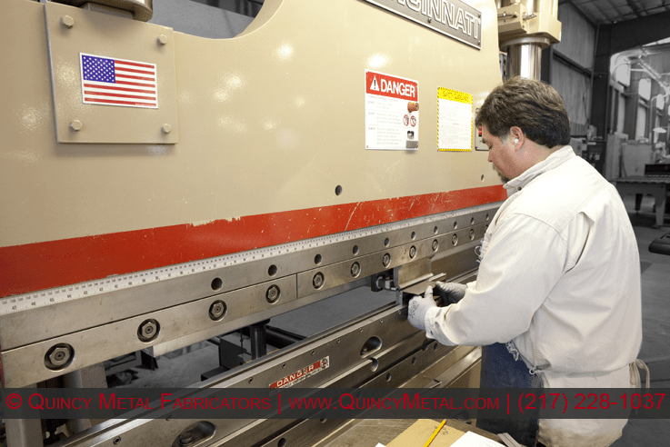 A Quincy Metal employee folds a smaller piece of sheet metal on a 130 ton Cincinnati CNC press brake.