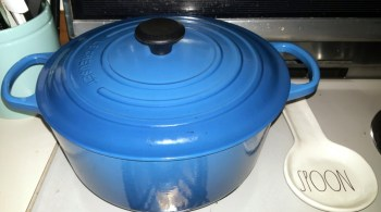 Blue Le Creuset sitting on stovetop