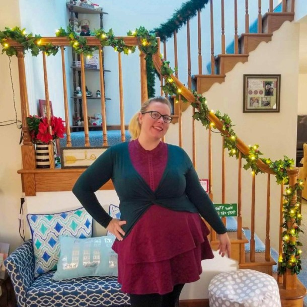 Chrissy wearing maroon and dark green in front of pre-lit garland