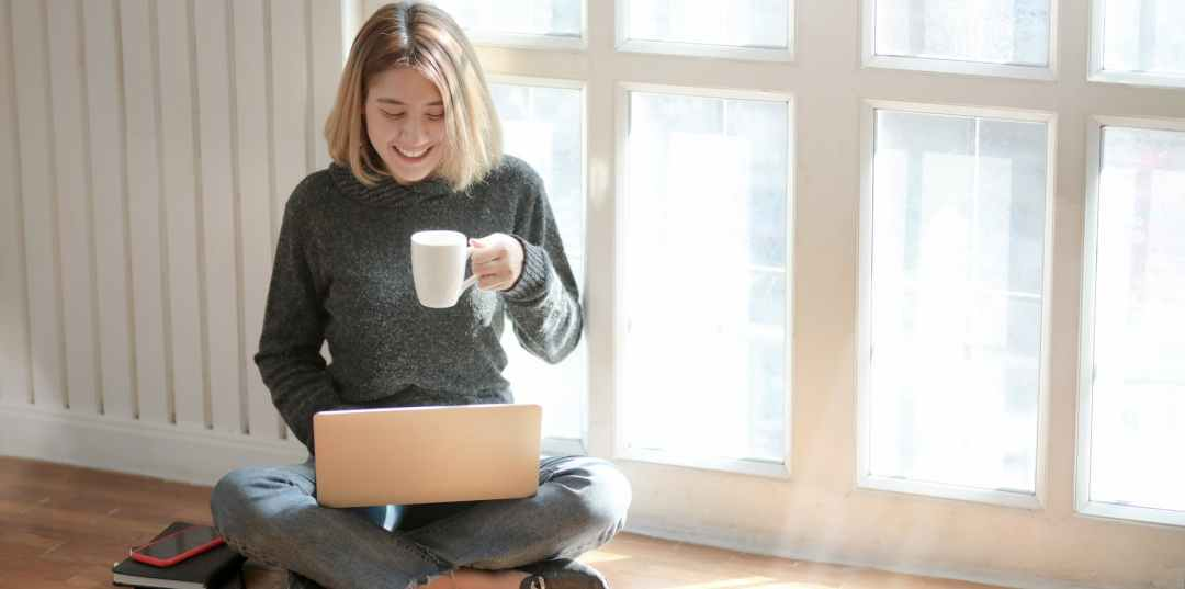 Woman in a grey sweatshirt working on her blog on her laptop.
