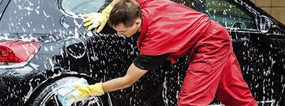 A car valeter washing a black car