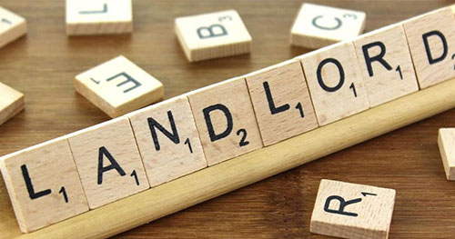 Commercial Property Insurance represented by the word landlord on a scrabble board