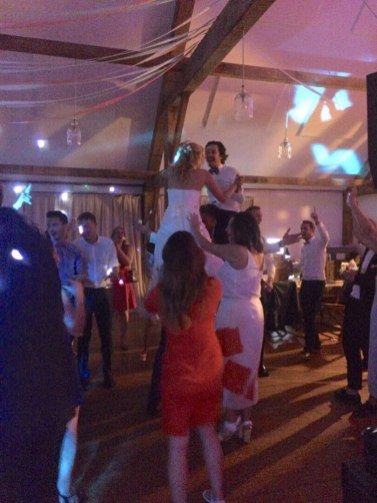 Bride and groom supported by wedding guests at the end of their evening party in Cornwall