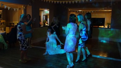 Bride dancing in circle of friends at a wedding disco at Treglos Hotel, Padstow