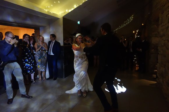 Energetic first dance at a winter wedding with Christmas lights at Trevenna, Liskeard