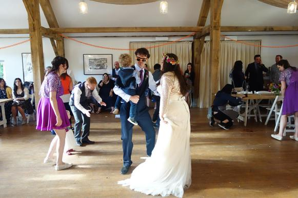 Cool couple with child during their first dance at Nancarrow Farm wedding in Cornwall