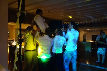 Groom getting lifted by friends on the dancefloor during Cornish wedding party