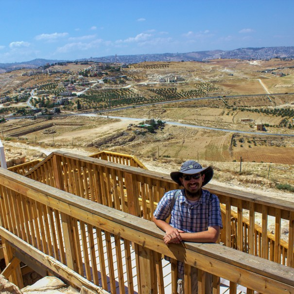 wooden banister guy with hat mountain range in background