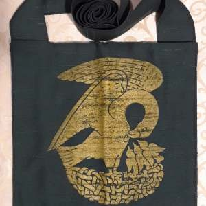 Bag made from green fabric, lined, printed with a hand carved 15th century Pelican stamp in gold.