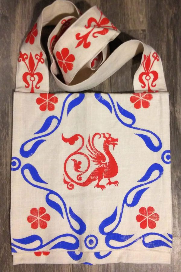 Bag made from white cotton fabric, lined with white cotton fabric & hand printed in red & blue with a hand carved 13th century dragon and other medieval inspired stamps.