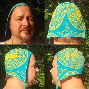 Limited edition large teal linen coif/arming cap, handprinted in yellow with a handcut 11th century lioness print & 12th century filling stamp.