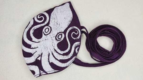 Purple/magenta colored linen octopus face mask with long ties and white octopus print. New, pre-washed fabric, ready to wear and machine washable!
