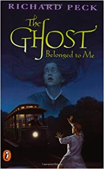 Cover of book 'The Ghost Belonged to Me'. Image shows a tram approaching a boy in pyjamas whilst a ghostly girl hovers in the sky overhead.