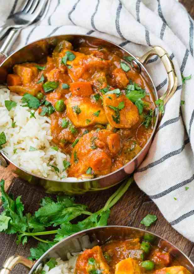 Chicken in a creamy coconut tomato sauce with vegetables, served with rice.