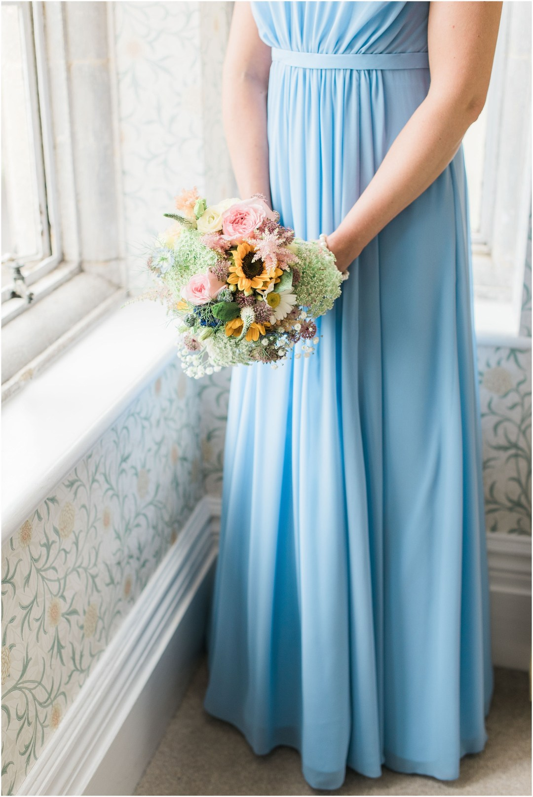 bridesmaid wearing a pastel blue dress and holding a floral bouquet