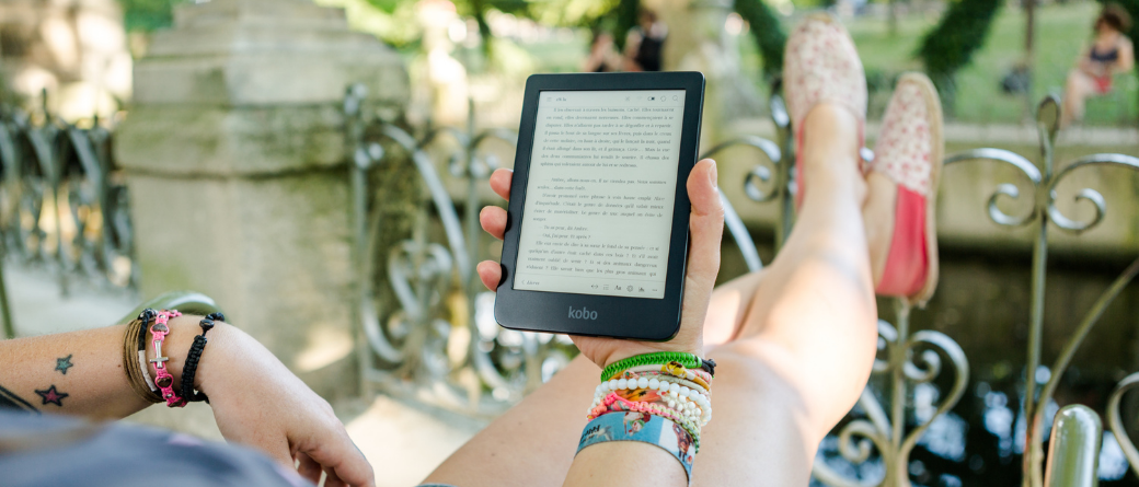 A tattooed woman wearing bracelets, with her feet up against a metal fence, reading on a Kobo ereader