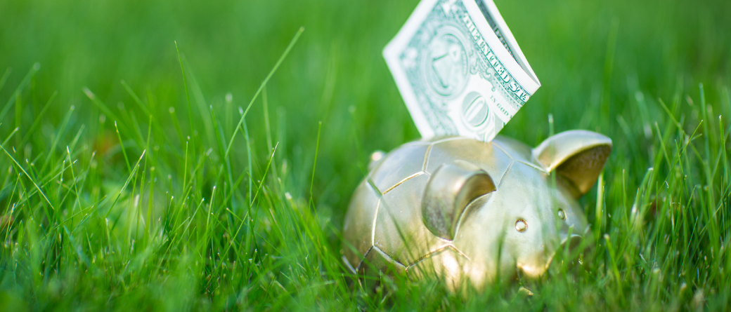 A gold piggy bank in green grass, with a dollar sticking out of the top