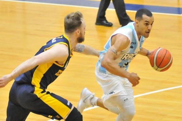 Jugador de básquet de Racing corre con la pelota.