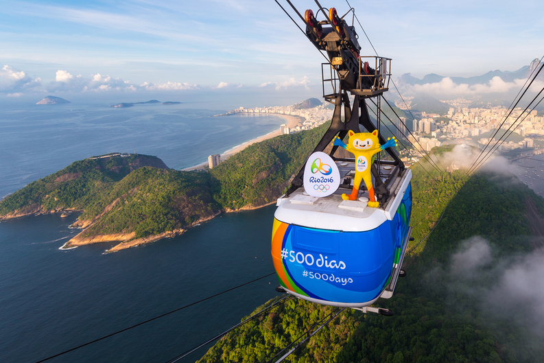RIO DE JANEIRO, BRAZIL - MARCH 23: In this handout image provided by Rio 2016, Olympic mascot, Vinicius, rides from the top of the Sugarloaf cable on March 23, 2015 in Rio De Janeiro, Brazil. Rio de Janeiro celebrates 500 days to go until the Rio 2016 Olympic Games, the first to be staged in South America (Photo by Alex Ferro/Rio 2016 via Getty Images)