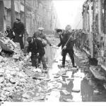 Scherl: ADN-ZB/Archiv II. Weltkrieg 1939-45 Berlin nach dem Luftangriff am 3.2.1945. Ein Wasserrohr barst beim Angriff. Die Wassermassen überschwemmten die Oranienstraße. Passanten bauen aus Trümmersteinen neben einer zerstörten Straßenbahn einen Notsteg.