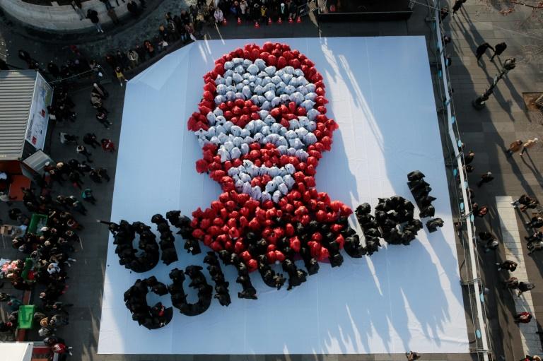 Des gens habillés en blanc et en rouge forment le portrait de l'Abbé Pierre, tandis que d'autres habillés en noir forment le slogan