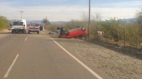 Los médicos, detrás del auto volcado, atienden a uno de los heridos del accidente vial ocurrido esta mañana. Foto: El Tribuno