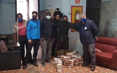 Migrantes que enfrentan orden de desalojo reciben viandas solidarias de AEBU
