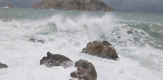 Pla mitjà d'una onada impactant contra una roca amb les illes Medes de fons aquest diumenge 10 de gener de 2020 a l'Estartit | Imatge de l'ACN