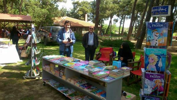 Το βιβλιοπωλείο Χαραλαμπίδη στην γιορτή με γεμάτο πάγκο από χρωματιστές εικόνες παραμυθιών και βιβλίων.