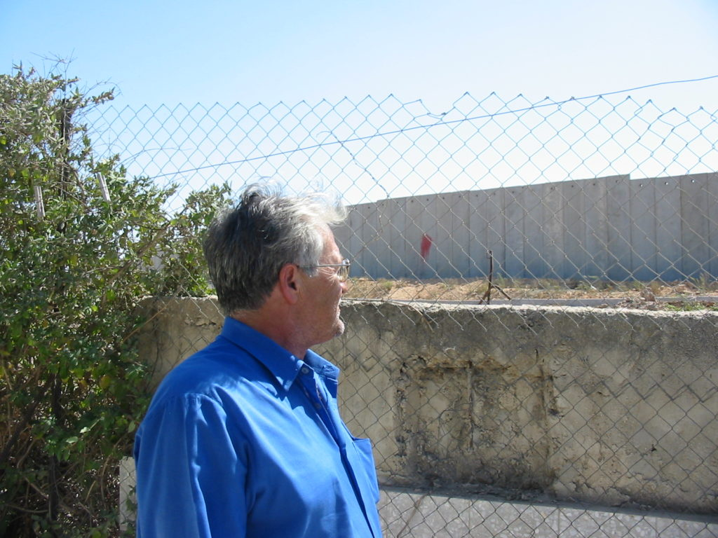 Dr. Sami Ass'ad looking at the Wall in his backyard