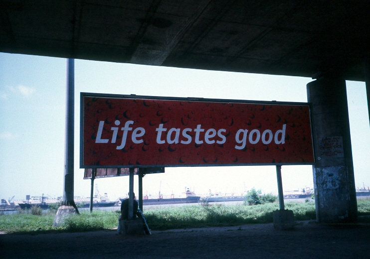 Billboard under a fly-over in downtown Lagos, with the port in the background