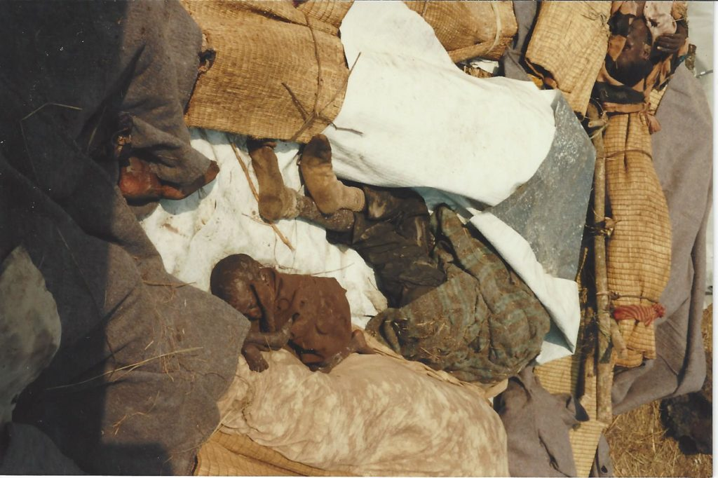 Dead child on a pile of corpses awaiting burial