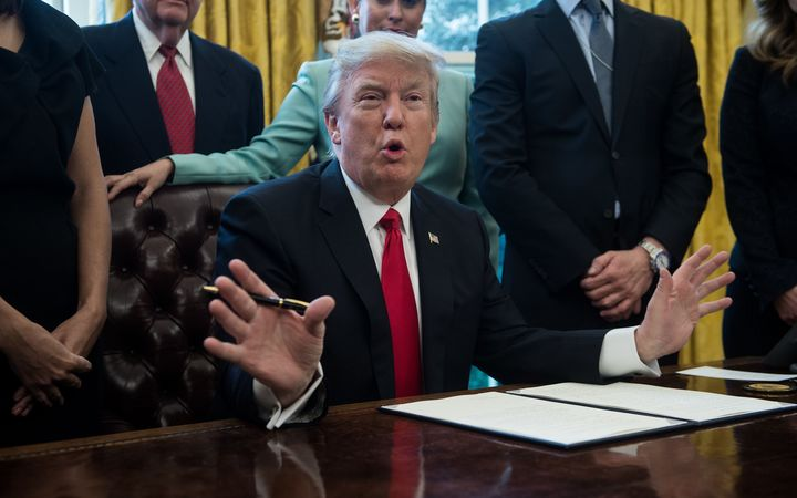 US President Donald Trump signs an executive order with small business leaders in the Oval Office at the White House in Washington DC on January 30.