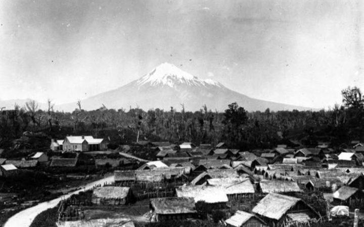 Parihaka Pa, circa 1900, with Mount Taranaki - taken by an unidentified photographer.