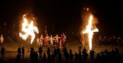 """Miembros del Ku Klux Klan queman una cruz y una esvástica durante un acto para exaltar el """"orgullo blanco"""" cerca de Cedar Town, Georgia, el 23 de abril del 2016. 150 años después de su nacimiento, el KKK sigue vigente, aunque con muchos menos afiliados que en sus mejores momentos, y se enfoca en su oposición a la inmigración, no en los derechos civiles de los negros. (AP Photo/Mike Stewart)"""