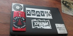 Collection of XRAY.fm stickers on laptop at community radio station. Photo: J. Waits