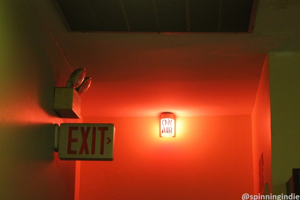 The glow of the on-air sign at community radio station KABF. Photo: J. Waits