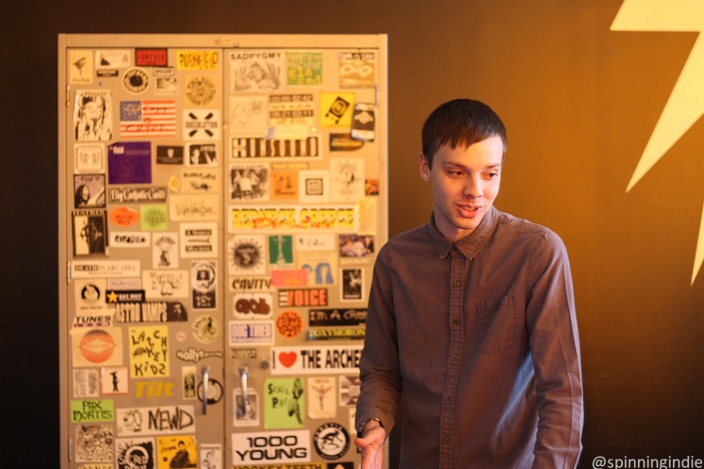 Soren Spicknall in front of sticker-covered cabinet at WIIT. Photo: J. Waits