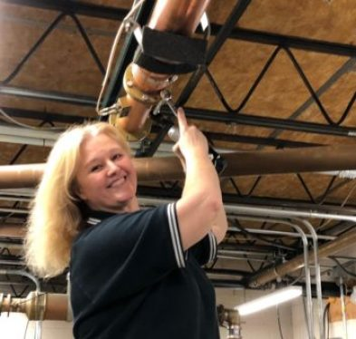 Photo of Sherri Powers working on part of the transmission system for Beasley Detroit