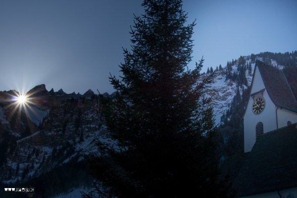 Die Sonne scheint durch das Martinsloch auf die Kirche von Elm
