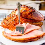 slice cut ham with brown sugar glaze and fork
