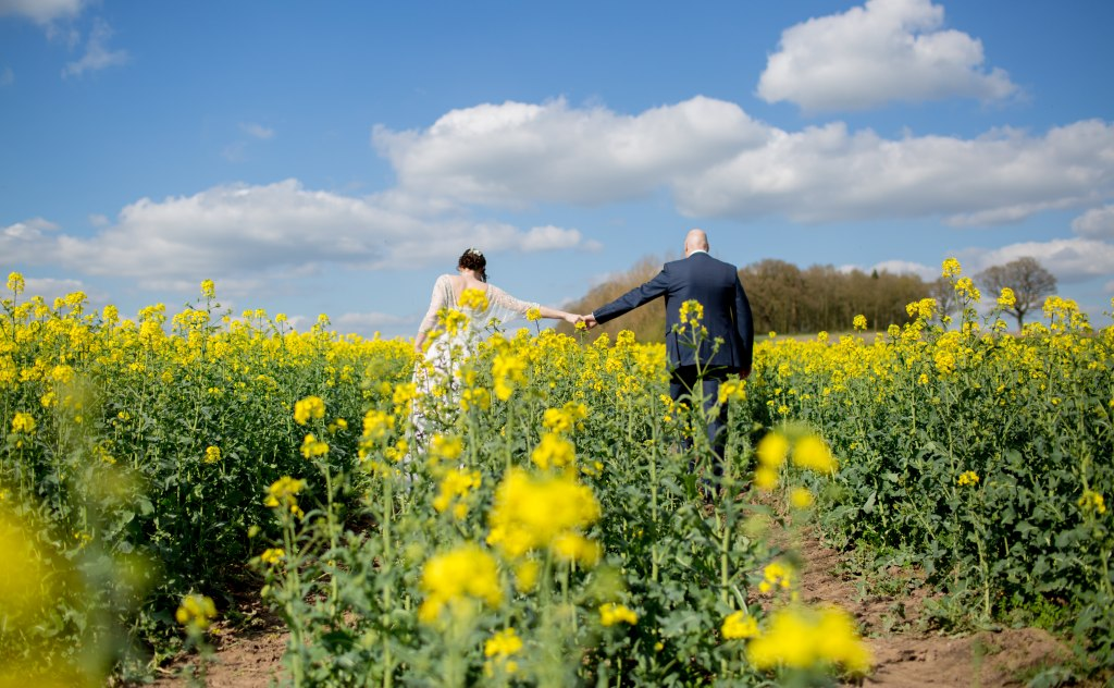 bride and groom holding hands walking through field