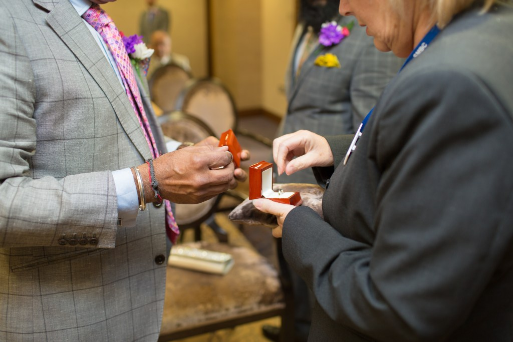 father of bride passing rings to registrar