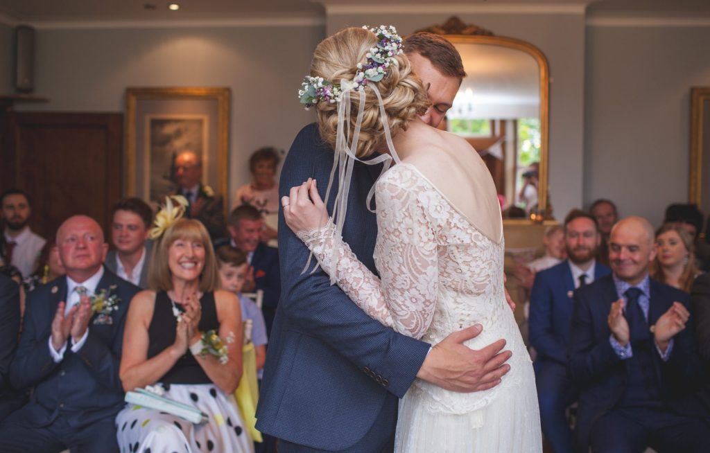 bride and groom embrace during wedding ceremony